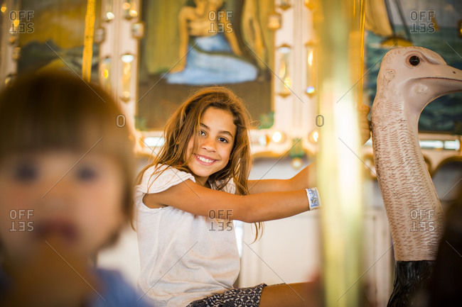 Smiling girl sitting on a carousel