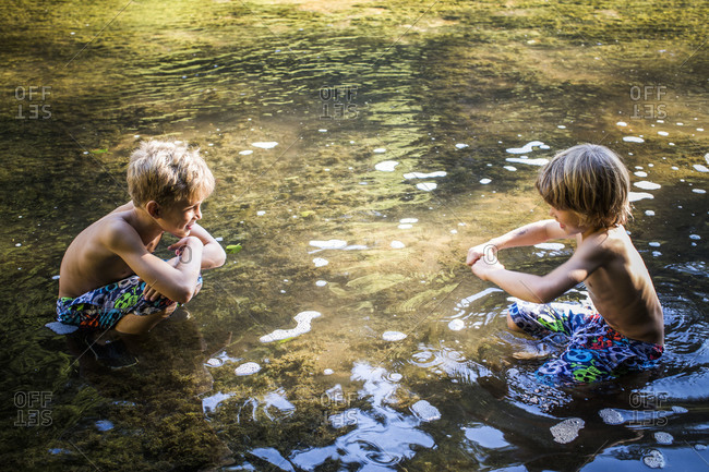 Brothers playing in the river