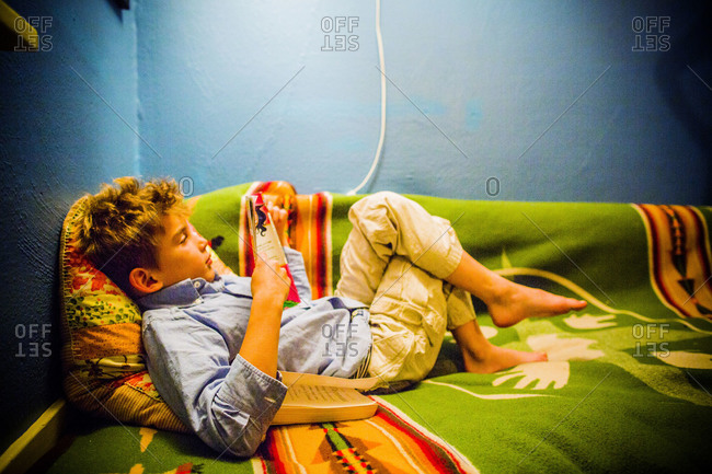 Boy reading a book in his bedroom