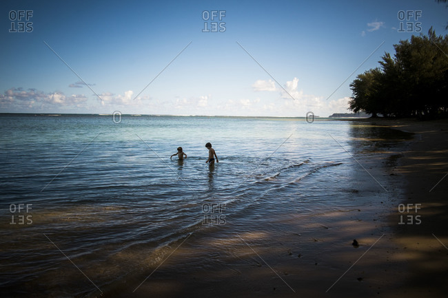 Children wading into the ocean