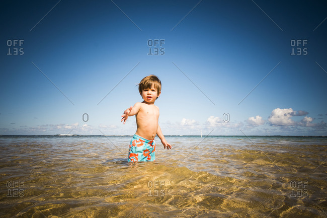 Boy standing in shallow water on the beach