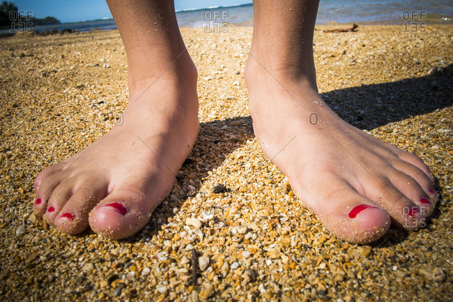 Close up of the feet of a teenager on the beach