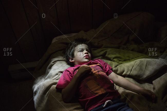 Boy lying awake in his bed