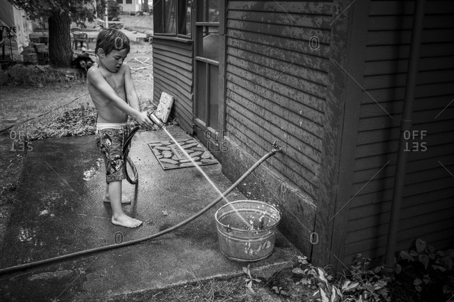 Child filling a bucket with water
