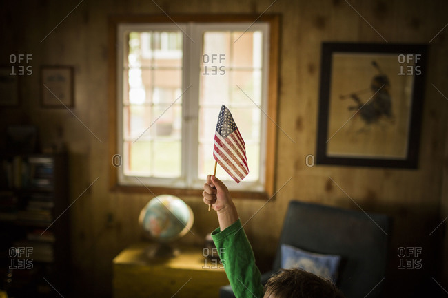 Child holding high an American flag