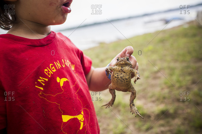 Young boy holding a toad