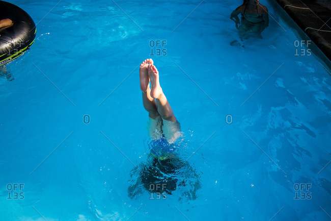 Girl jumping into a swimming pool