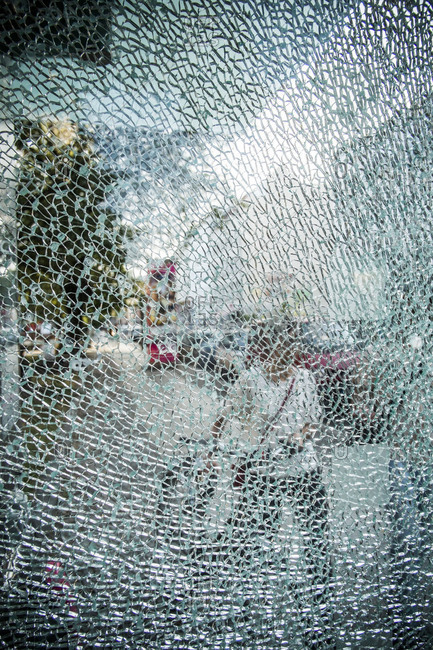 Person's reflection in shattered mirror