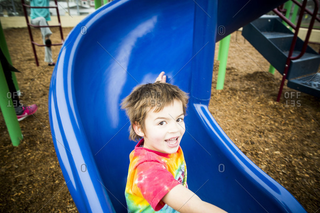 Young boy on a blue slide