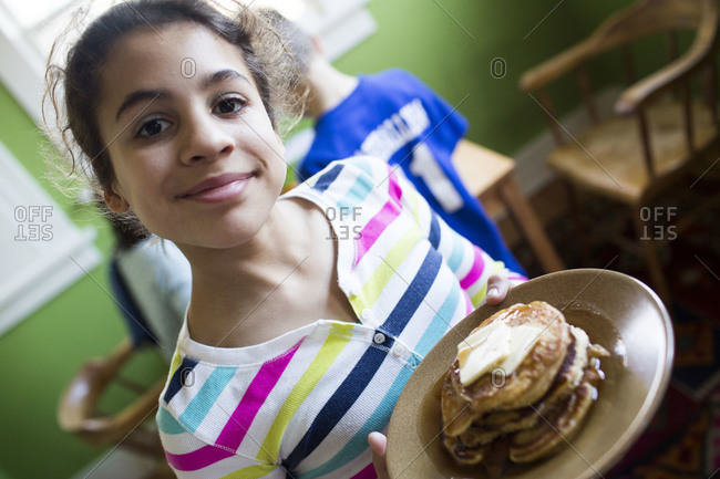Young girl holding pancakes - Offset