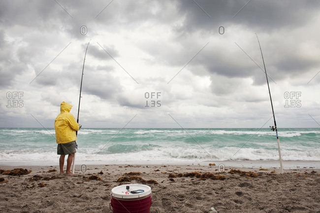 Surf fisherman on beach with stormy seas