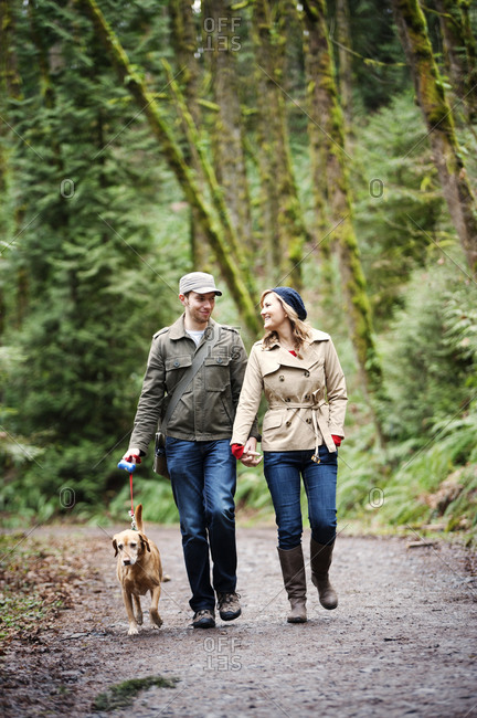 Couple walking hand-in-hand on forest trail with dog