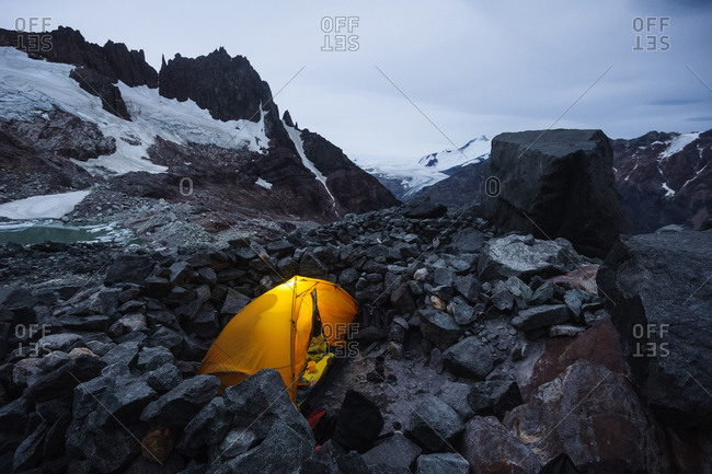 A tent glows with headlamps at the Piedra Negra bivy, El Chalten, Patagonia, Argentina