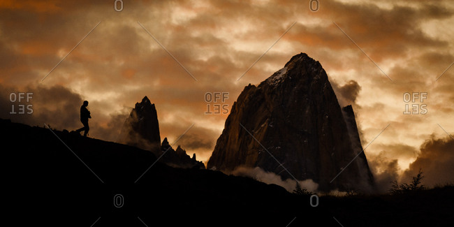 A lone hiker on a ridge below the imposing Cerro Fitzroy at sunset, El Chalten, Patagonia, Argentina