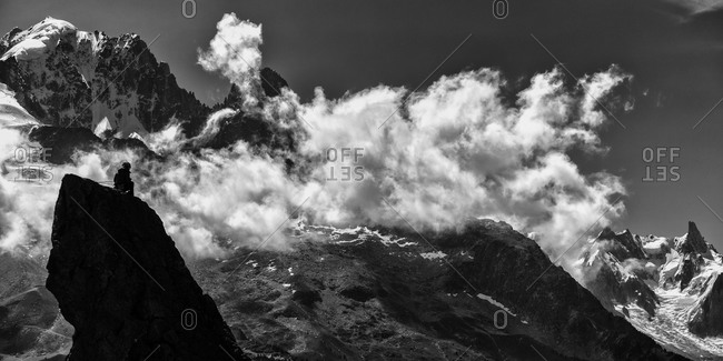 A mountain climber on the summit of Aiguillette d'Argenti�re, with Aiguille Verte and the Drus in the background, Chamonix, France