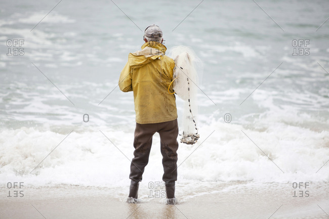 Fisherman with net in the surf