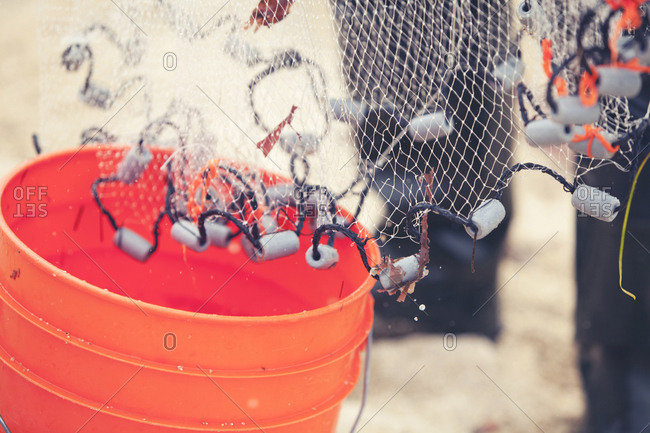 Fisherman with net over red plastic bucket