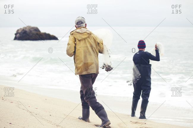 Two men casting for fish with nets from the beach