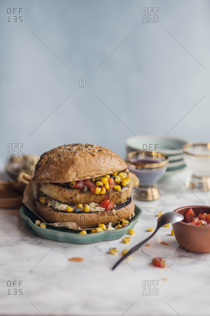 Southern pork burger with salsa and corn served on kitchen counter