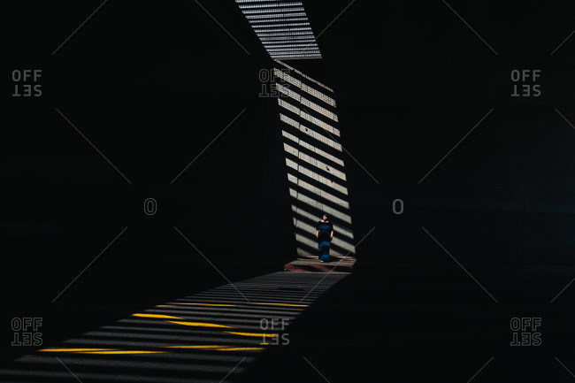 Woman standing in the shadows on the sidewalk