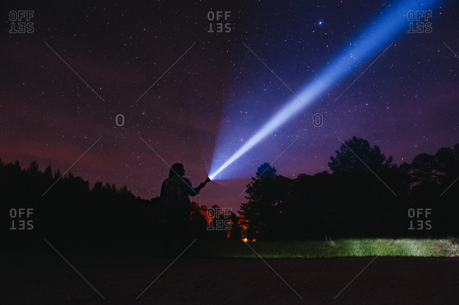Woman silhouetted against night sky with flashlight