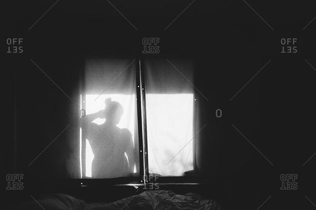 Black and white silhouette of woman in window