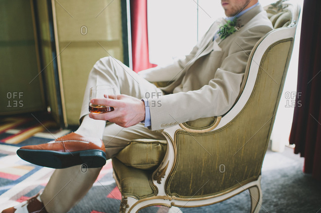Groom sitting in classy armchair with a drink