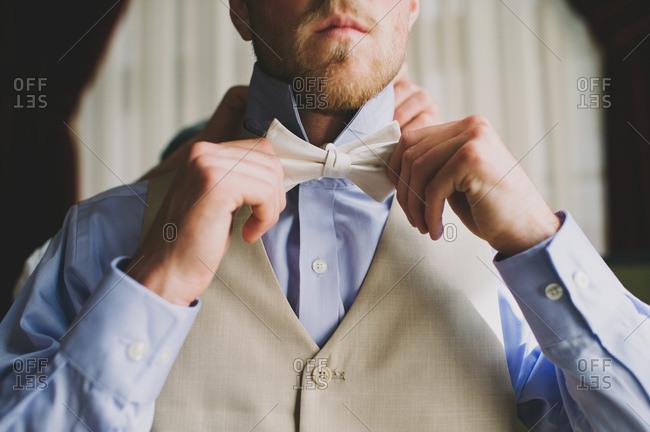 Groom getting dressed before his wedding