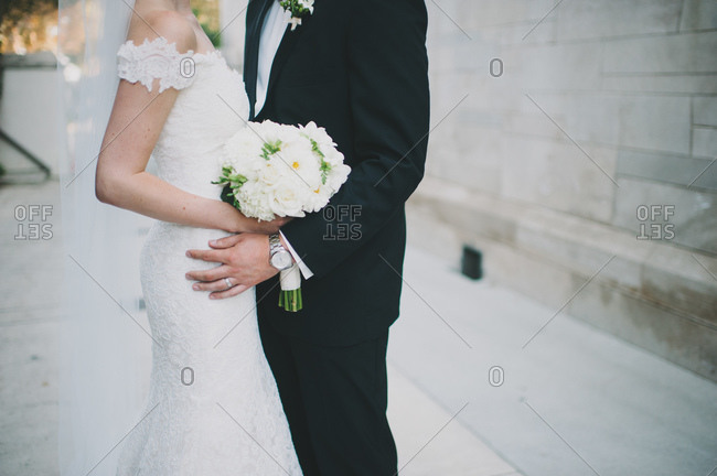 Husband and wife hugging at a wedding