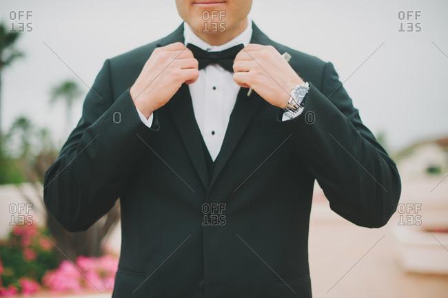 Groom adjusting bow tie at wedding