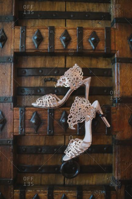 Pair of wedding shoes hanging on wooden door