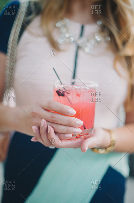 Woman holding beverage in a fancy dress