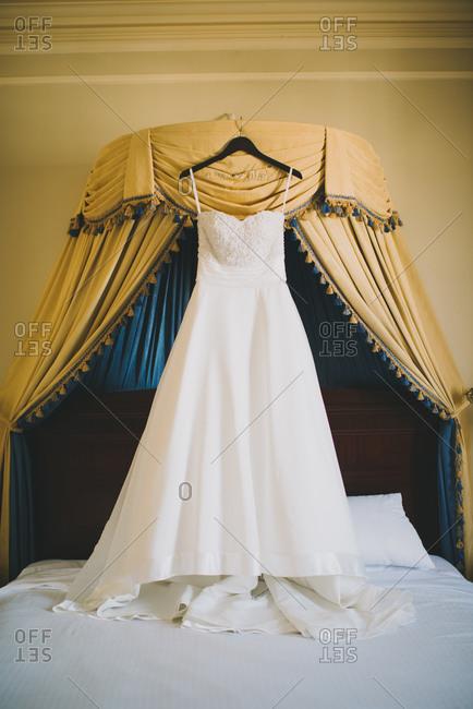 Bridal dress hanging over bed
