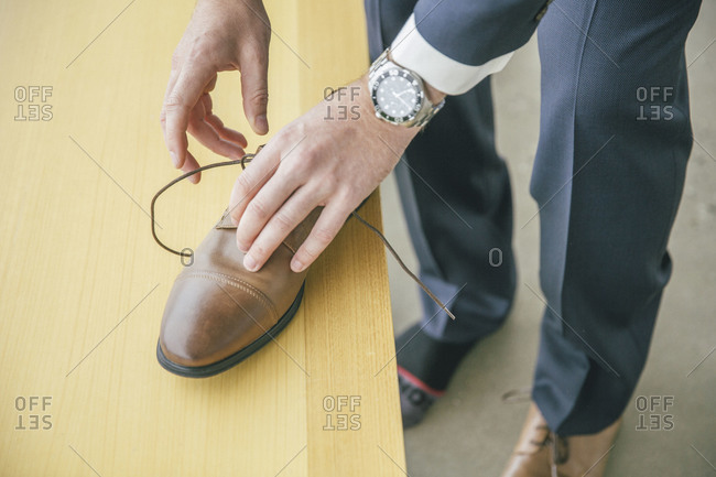 Man adjusting the laces of  a shoe