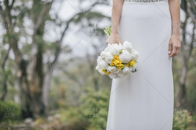 Bride in simple dress holding flower bouquet