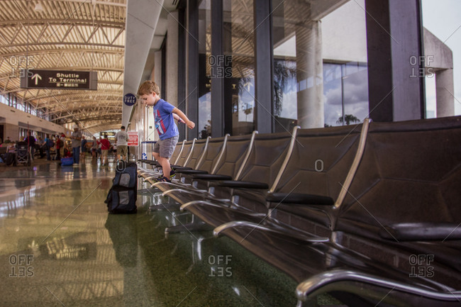 Boy standing on seats in airport terminal