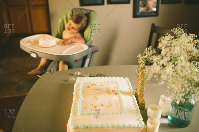 Little girl sleeping next to her birthday cake