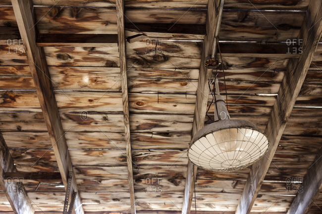 Light fixture hanging from a wooden ceiling