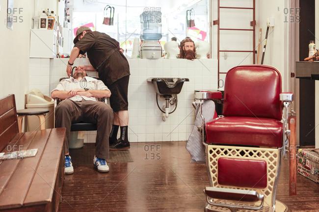 Albuquerque, New Mexico - April 25, 2012: Barber attending client in barber shop