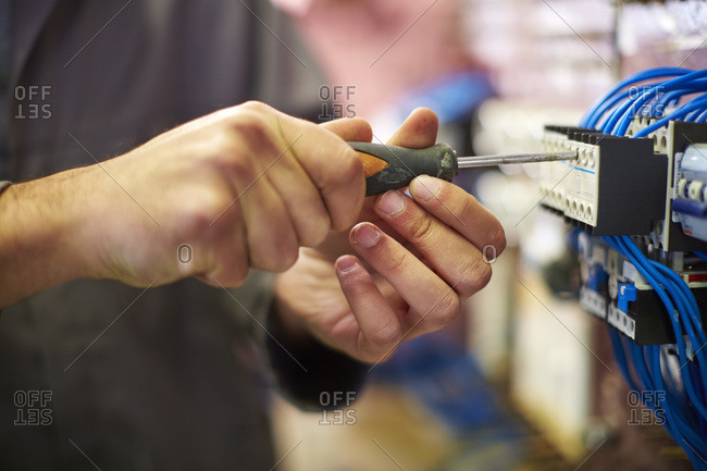 Close-up of electrician working with screw driver