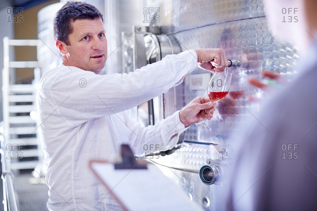 Wine maker tapping wine from tank