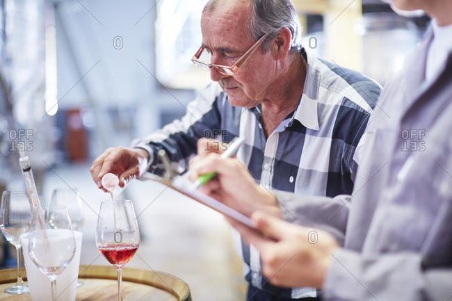 Wine maker testing wine blend
