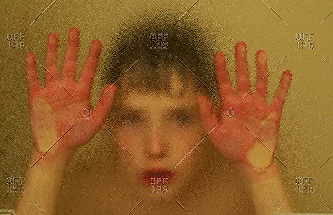 A young boy up against the glass of a shower