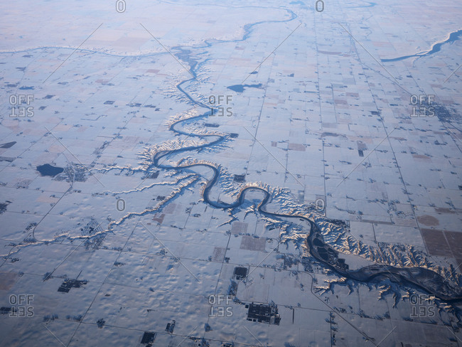 A view of a river cutting through snowy fields in southern Alberta, Canada