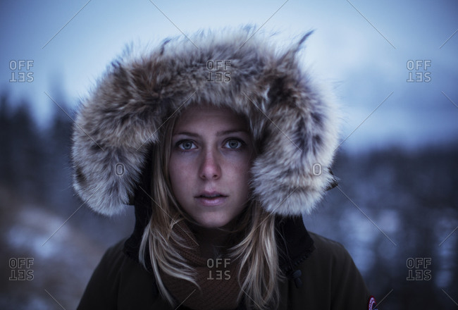 A pretty young blond woman keeps warm in her winter parka in Banff National Park, Alberta