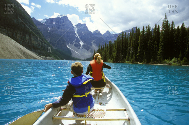 A young boy and his mother explore Moraine Lake in a canoe, in Banff National Park, Alberta