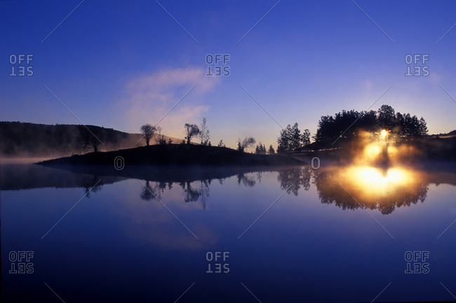 Dawn breaks over a lake in the  foothills of the Canadian Rockies