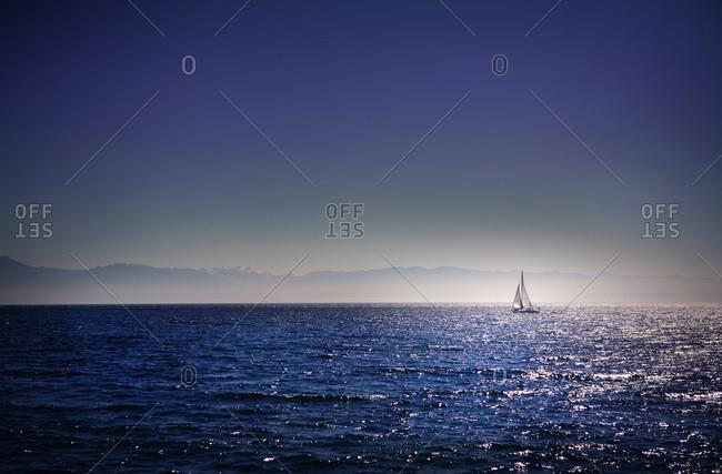 A sailboat cruises the Juan de Fuca Strait near Victoria, British Columbia