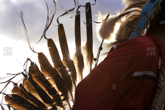 Eagle features shine in the sun on a traditional native head dress on the back of a native dancer in the Cypress Hills, Alberta,