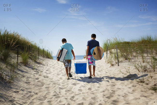 Boys carrying a cooler to the beach
